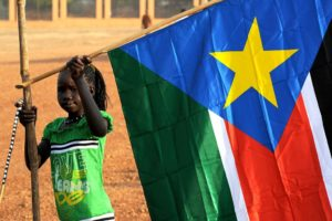 1280px-A_young_girl_hangs_the_South_Sudan_flag_(5925619011)